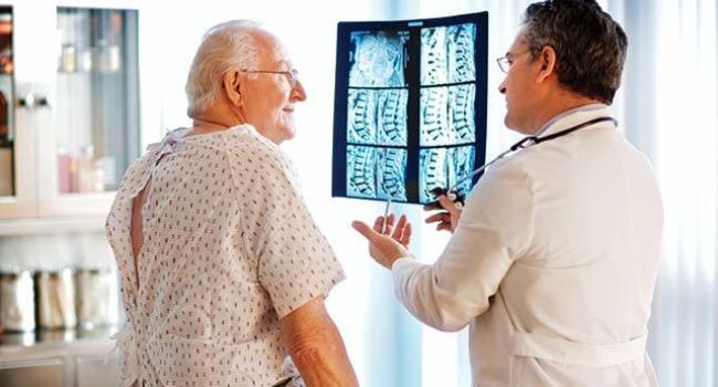 Acdf doctor talk to patient with spine xrays