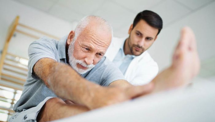 Doctor helping elder male stretch back